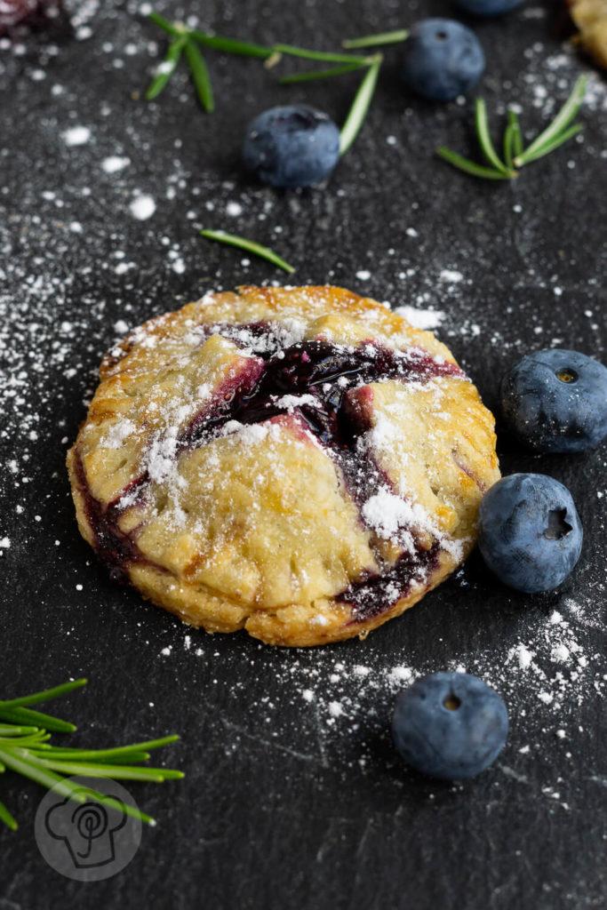 Leckere Handpies mit Blaubeeren und Rosmarin. Ein herrlich fruchtiger, sommerlicher Snack für das Picknick oder einfach so zum Naschen. Küchentraum & Purzelbaum | #blaubeeren | #heidelbeeren | #mürbteig