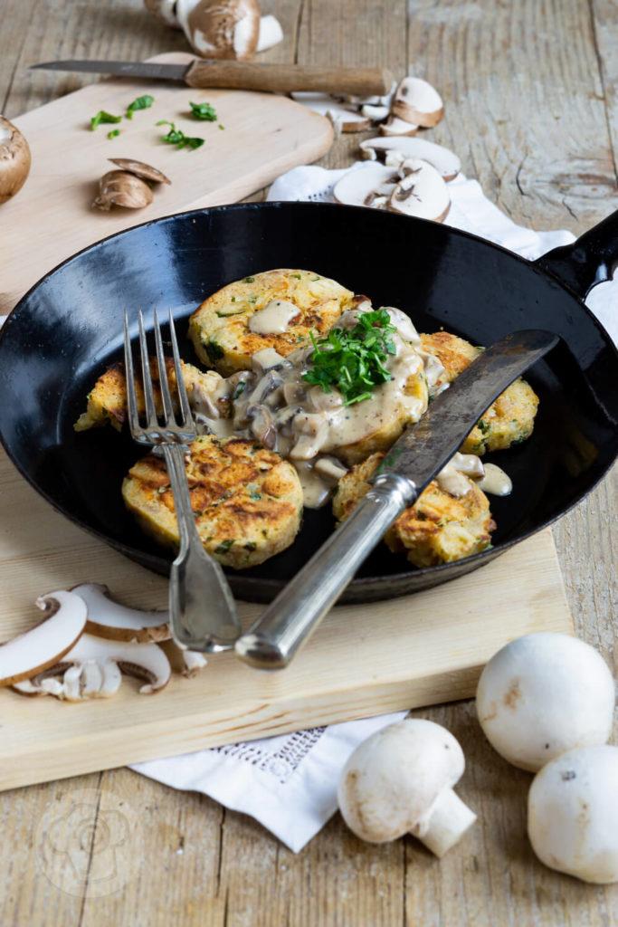 Serviettenknödel mit Pilzsoße und frischen Kräutern. Serviert in einer Pfanne.
