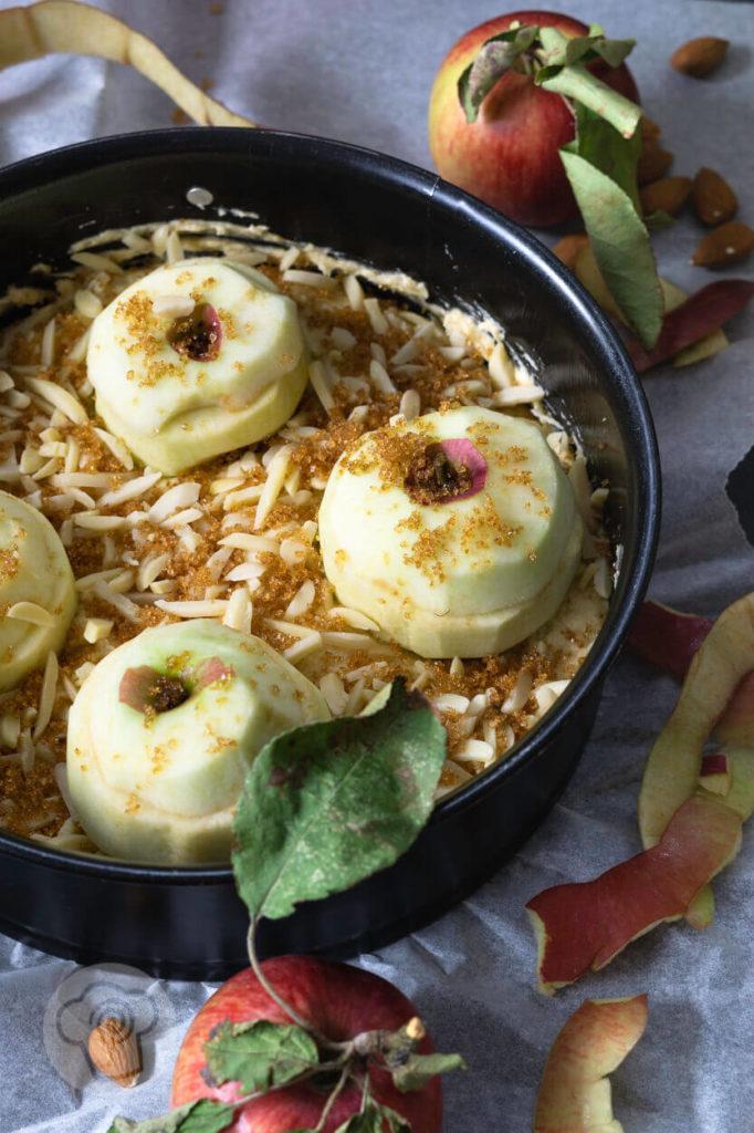 Bratapfelkuchen mit Äpfeln und Mandeln dekoriert, ungebacken