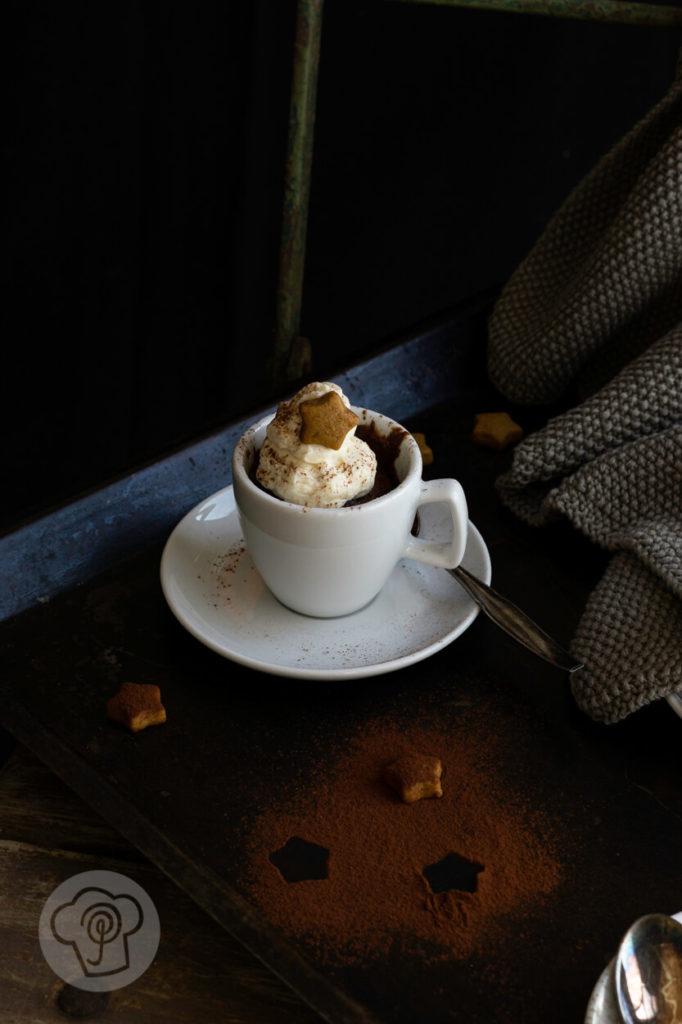 Weihnachtliche Schoko Tassenkuchen mit Lebkuchensahne in einer weißen Espressotasse, fotografiert auf einem Stuhl