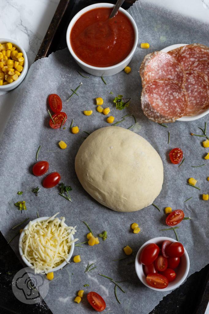Zutaten für eine leckere Calzone, Tomatensoße, Hefeteig, Käse, Tomaten, Salami, Mais
