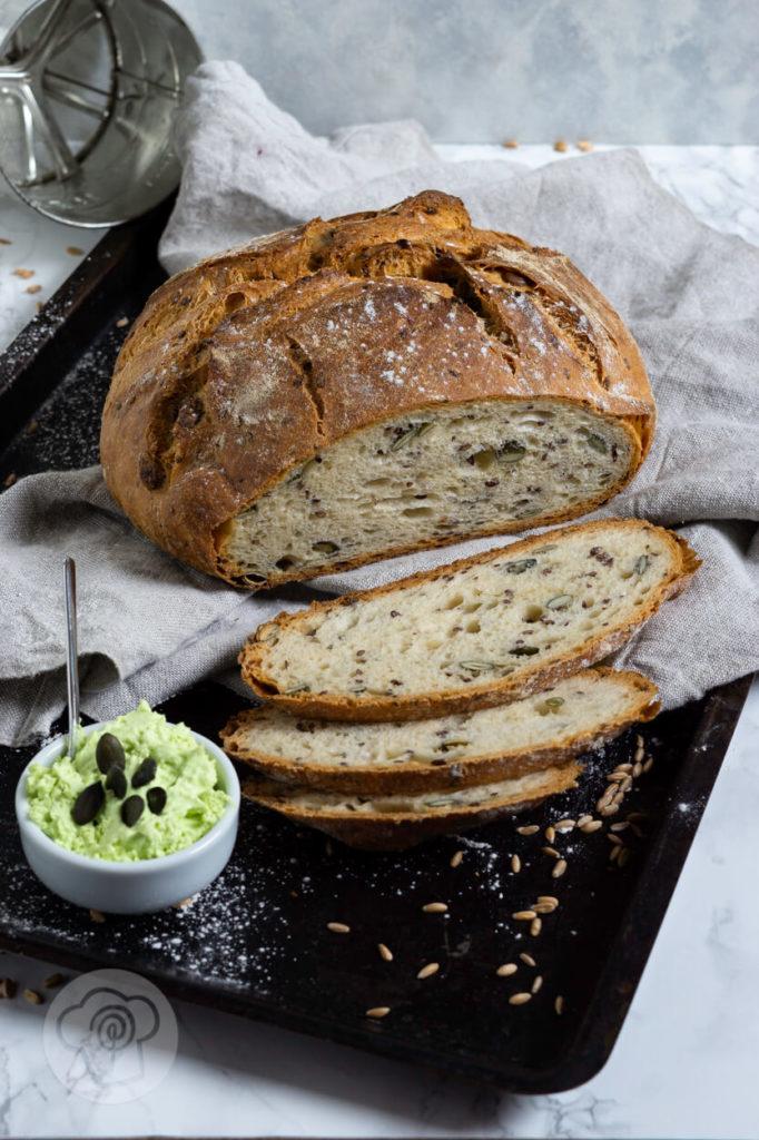 Dinkel Joghurt Brot mit Leinsamen und Kürbiskernen. Angeschnitten mit Aufstrich.