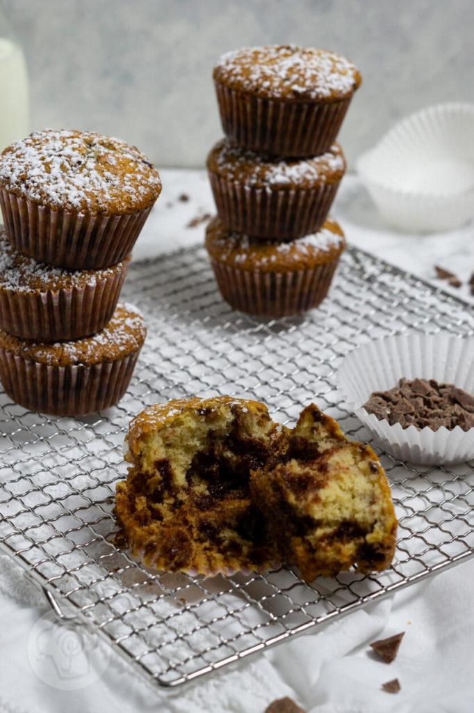 Muffins mit Schokostückchen gestapelt. Ein Muffin auseinander gebrochen.