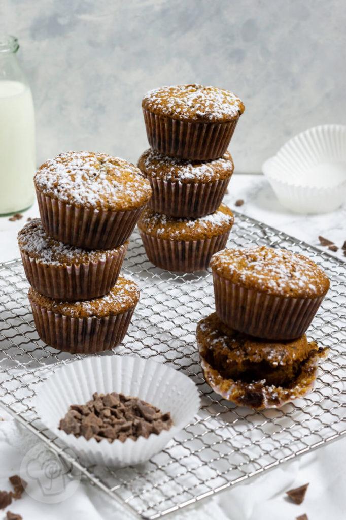 Muffins mit Schokostückchen, gestapelt, bei einem Muffin Papier halb entfernt