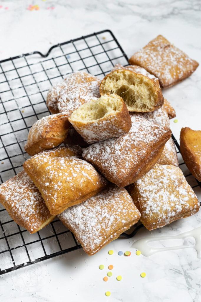 Rezept zum Backen: New Orleans Beignets. Die Qual der Wahl. Ihr könnt sie frittieren, im Ofen backen oder in der Heißluftfritteuse. Wie bereitet ihr das Faschingsgebäck am liebsten zu? Küchentraum & Purzelbaum