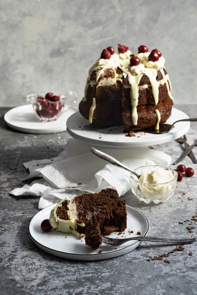 Rezept zum Backen. Schwarzwälder Kirsch Gugelhupf. Eine Neuinterpretation der klasischen Schwarzwälder Kirsch Torte. Probiert doch diesen einfachen und leckeren Kuchen mit Kirschen und weißer Schokoglasur einfach aus. Küchentraum & Purzelbaum