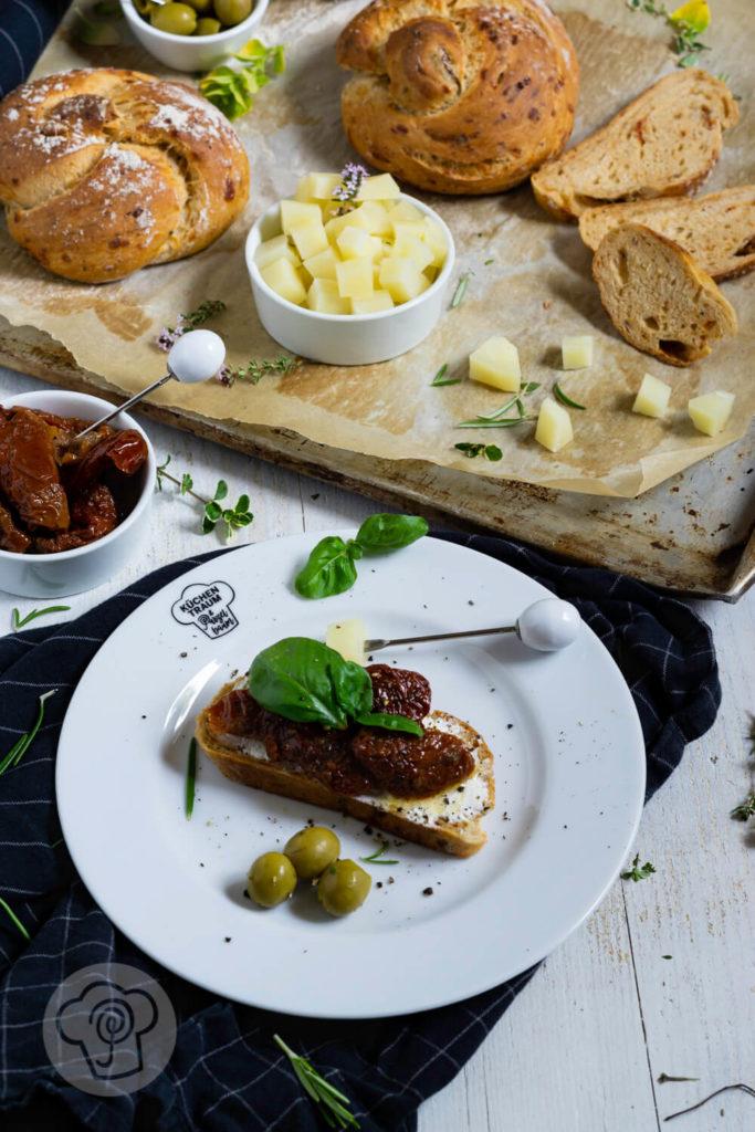 Scheibe Brot mit Frischkäse, getrockneten Tomaten und Basilikum