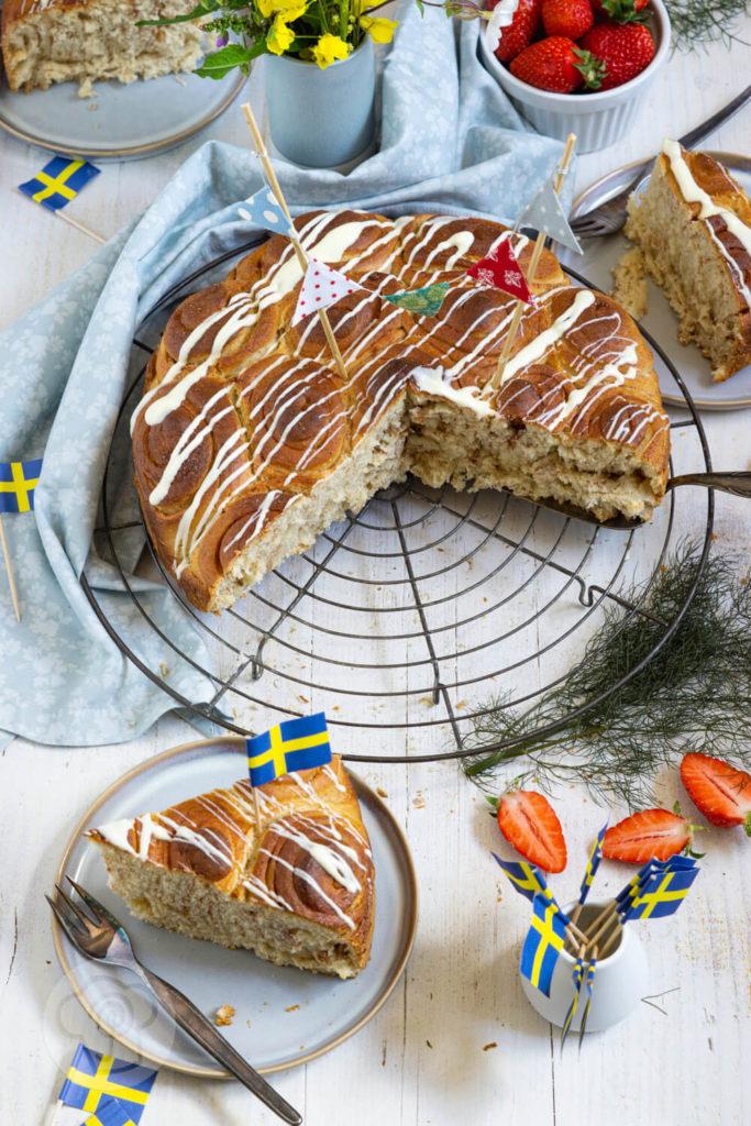 Zimtschneckenkuchen - angeschnitten, Stücke auf Tellern verteilt, Schwedenfähnchen