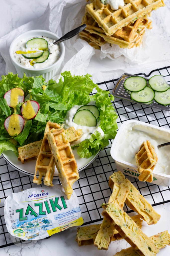 Zucchiniwaffeln in Streifen geschnitten mit Zaziki, Salatblättern und Gurkenscheiben angerichtet