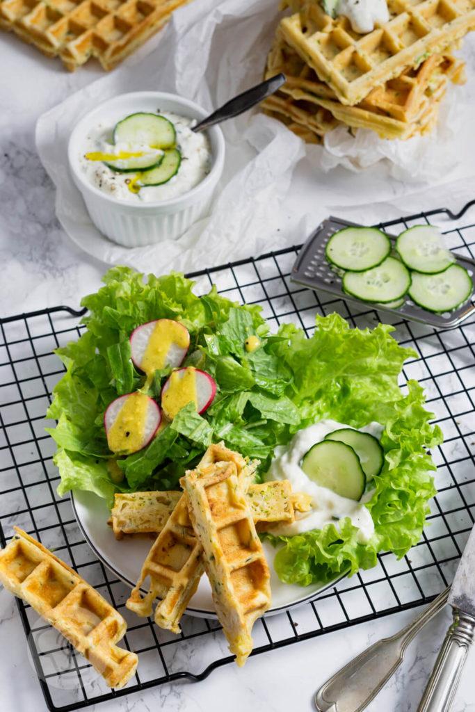 Zucchiniwaffeln in Streifen geschnitten mit Zaziki, Salat und Gurkenscheiben angerichtet