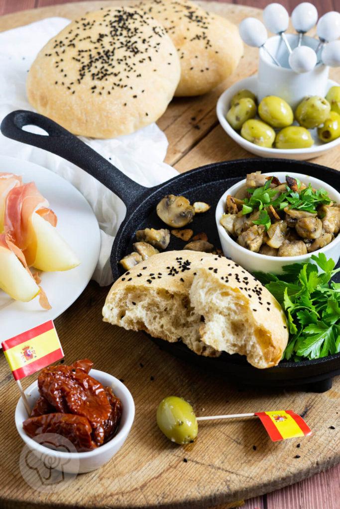 Gebratene Knoblauch Champignons mit Petersilie, Oliven, getrockneten Tomaten und Fladenbrot. Tapas serviert in einer gusseisernen Pfanne.