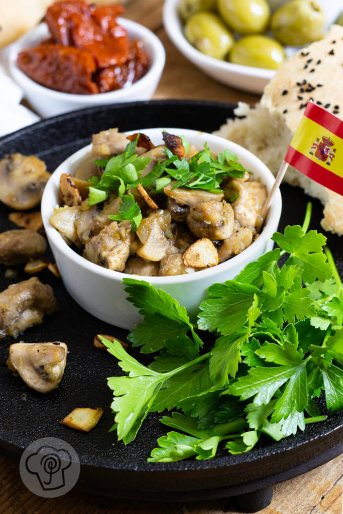 Gebratene Knoblauch Champignons mit Petersilie und Fladenbrot. Tapas serviert in einer gusseisernen Pfanne.