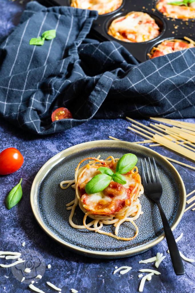 Spaghetti Muffin, einzeln auf einem Teller mit einer Gabel und Basilikum