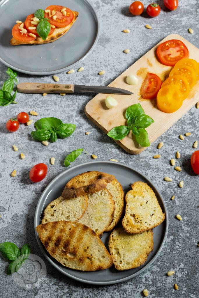 Geröstetes Brot mit Tomaten, Pinienkernen und Basilikum auf einem Teller