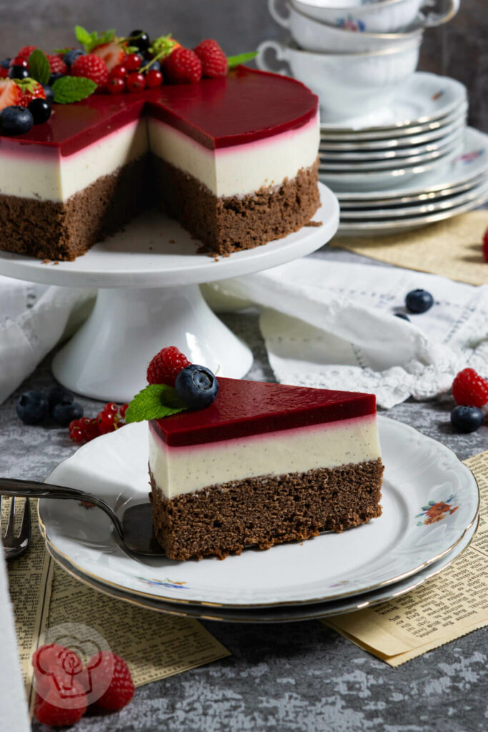 Stück Panna Cotta Torte auf einem Teller. Restliche Torte und Kaffeegeschirr im Hintergrund