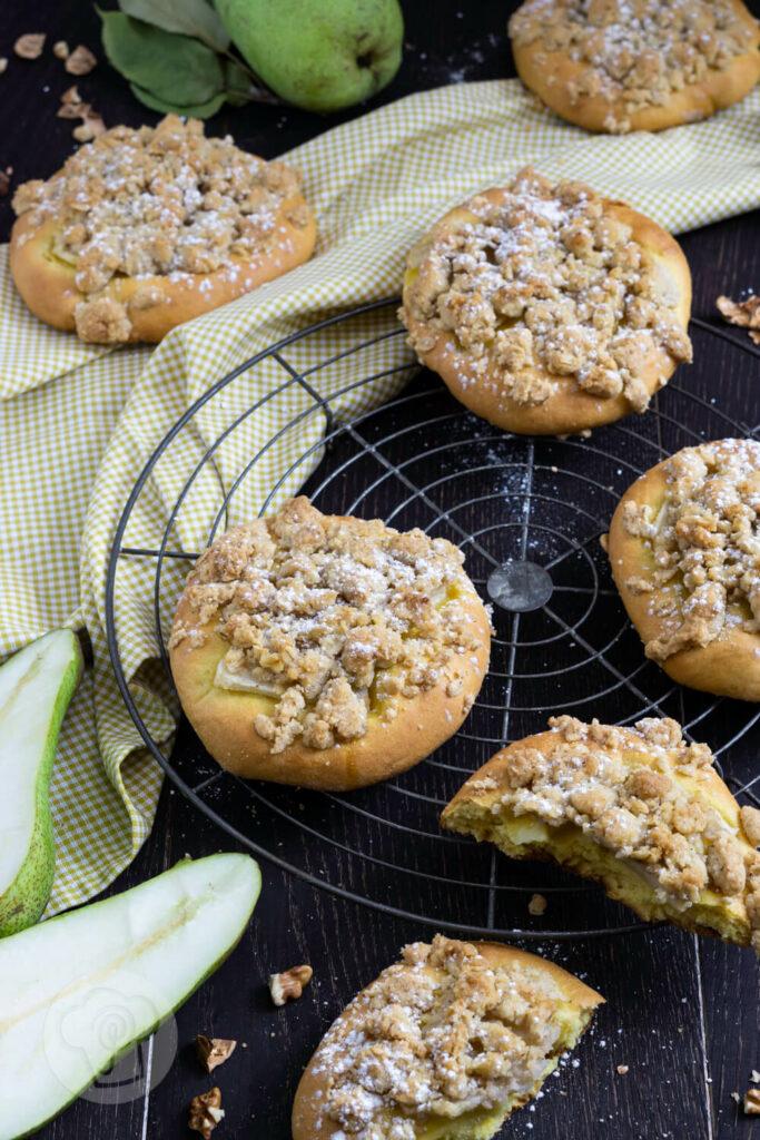 Kleine Streuselkuchen mit Birnen auf einem Rost.