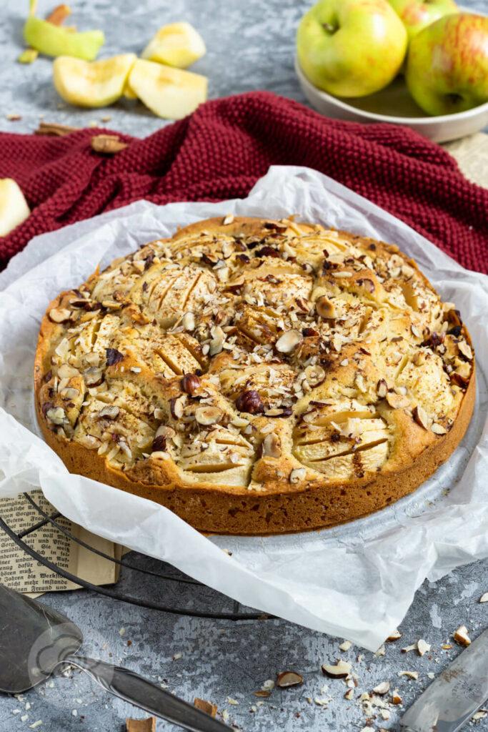 Einfacher gedeckter Apfelkuchen mit Nüssen. Kuchen auf dem Rost. Äpfel im Hintergrund.