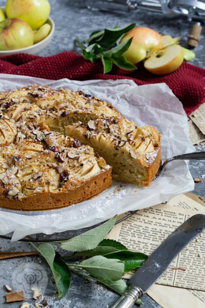 Einfacher gedeckter Apfelkuchen mit Nüssen. Ein Stück auf der Kuchenschaufel.