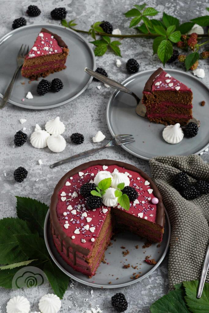 Brombeer Torte mit Schokolade auf einem Teller angeschnitten, mehrere Stücke auf Tellern. Brombeeren als Dekoration.