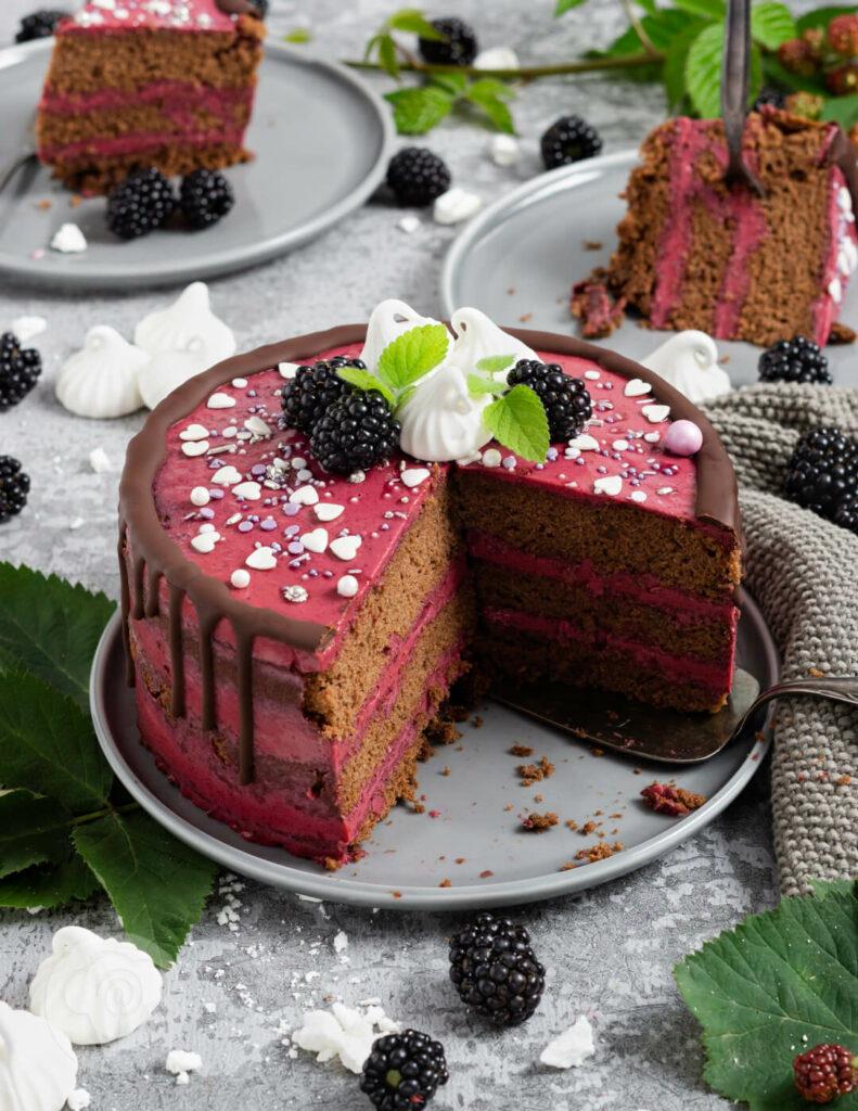 Brombeer Torte mit Schokolade auf einem Teller angeschnitten. Brombeeren als Dekoration.