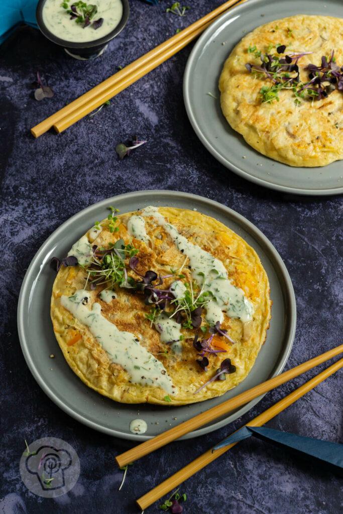 Japanische Pfannkuchen auf einem Teller mit Sprossen angerichtet.
