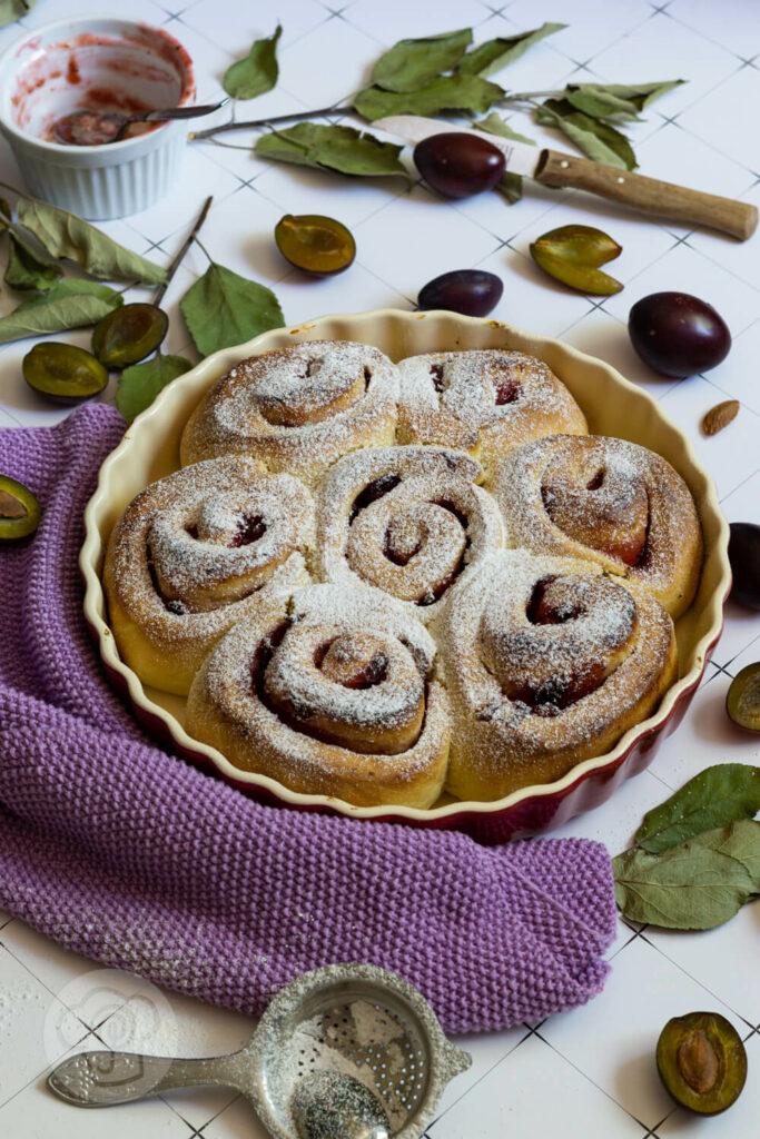 Hefeteigschnecken mit Pflaumen in der Form. Dazu aufgeschnittene Früchte, Blätter und Puderzucker.