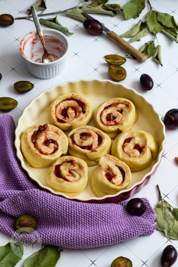 Rohe Hefeteigschnecken mit Pflaumen in der Form. Dazu aufgeschnittene Früchte, Blätter und Puderzucker.