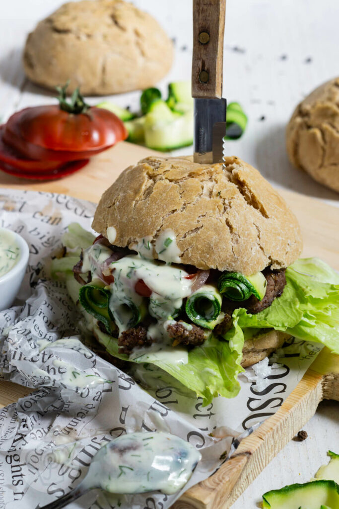 Zwiebel Burger mit Joghurt Mayonnaise mit Tomatenscheiben und Salat auf einem Brett serviert